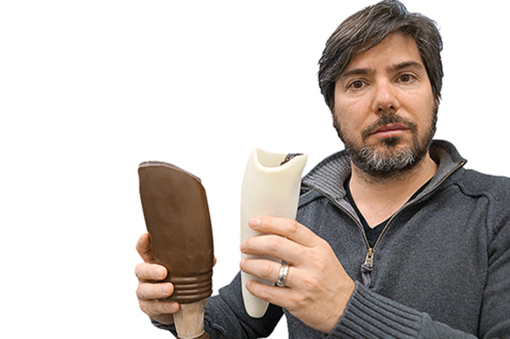Prof. Matt Ratto holds a conventional prosthetic socket (left) and one his lab printed. Source: University of Toronto