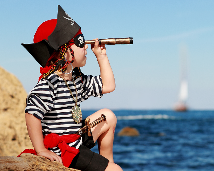 Pirate boy with telescope sitting on a rock. Source: Lesya_boyko/Shutterstock.com