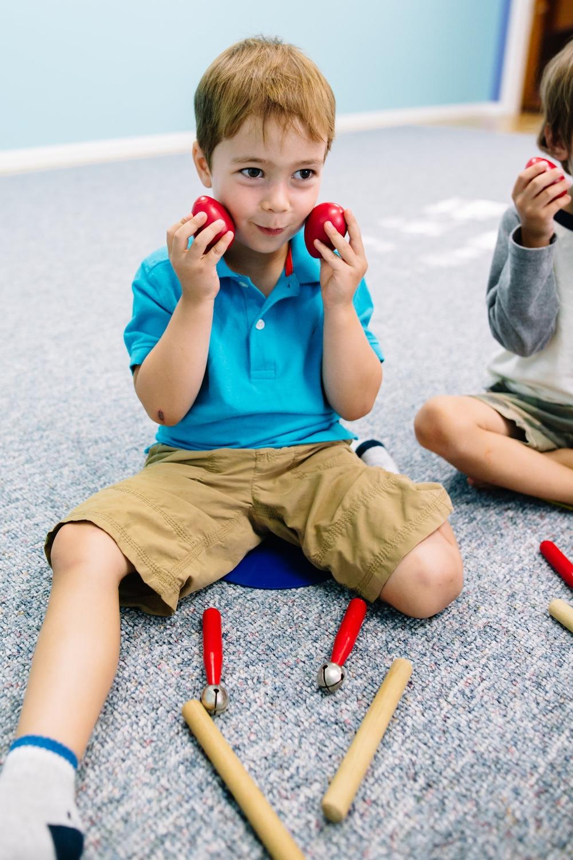 Kindermusik Preschool Music Class - Boy playing egg shakers