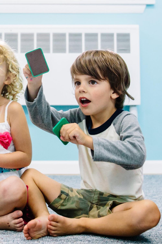 Kindermusik Preschool Music Class - Boy singing with sand blocks