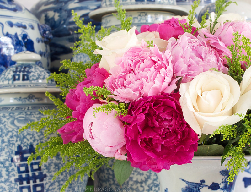 pink peonies and white roses in a blue and white beaker vase
