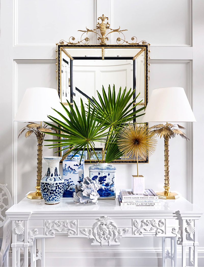 From House Beautiful's July/August issue, the vignette Suzanne Kasler designed with blue and white Chinese ceramics, palm leaves, palm tree lamps, and a white Chippendale console table is spectacular.