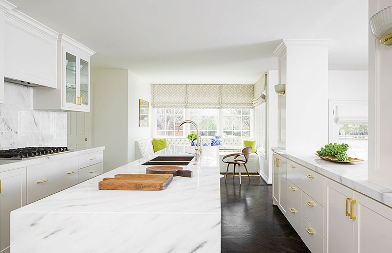 white kitchen and banquette with marble countertops and brass hardware