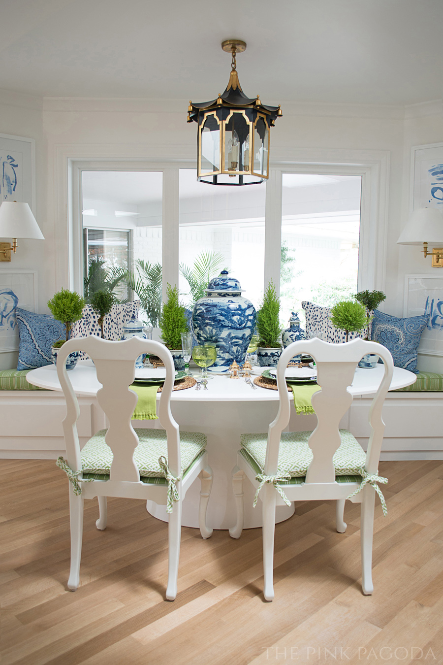 Banquette dining with blue and white created for The Pink Pagoda's One Room Challenge™. Art by Christina Baker, Coleen & Company pagoda lantern, and tabletop styling by Susan Palma.