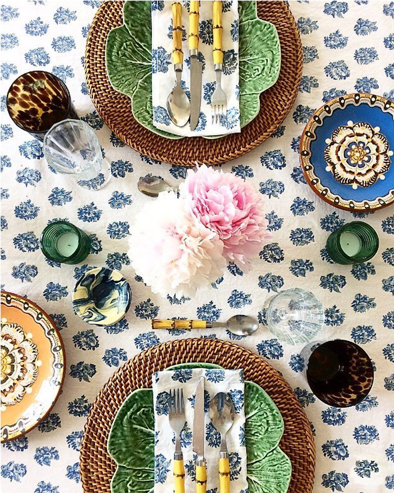 Eclectic global tabletop with Indian blue and white tablecloth and Portuguese dinnerware.