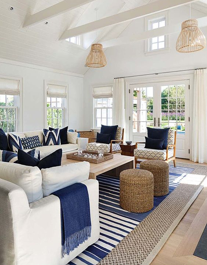 True divided light windows and french doors in this blue and white coastal sunroom.