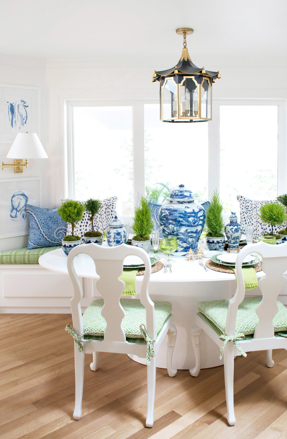 Blue abstract paper pieces by Christina Baker, pillows, and blue and white Chinese ceramics add the perfect amount of blue to this breakfast banquette.