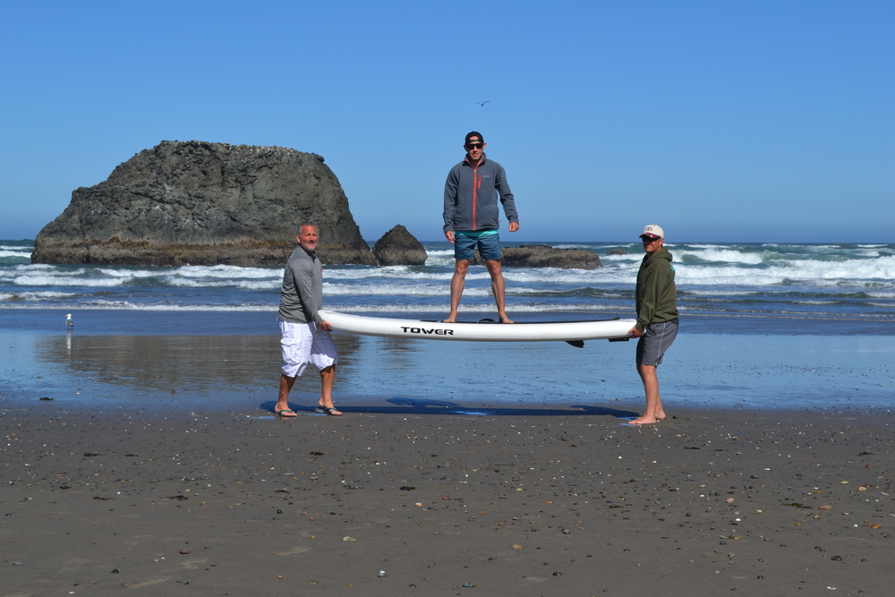One of our co-founders Scott took the family to the Oregon Coast recently.  Somehow he was able to sucker Jeff and Rick into holding him and the board up so he could demonstrate just how rigid our inflatable boards are.
