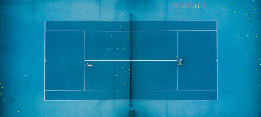 A Tennis player takes time out form the hustle and bustle of City life in China.