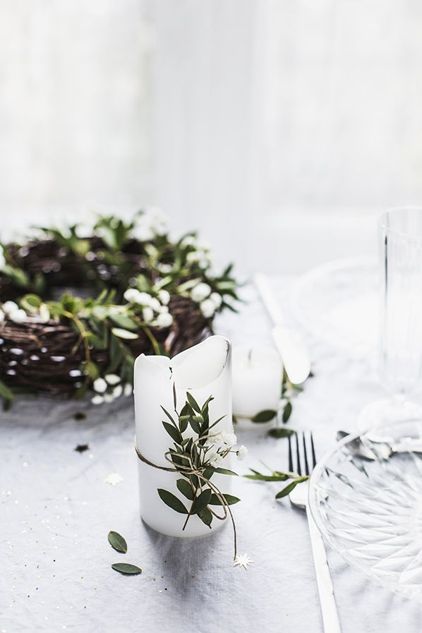 "The slogan ""bringing the outdoors in"" is an understatement for todays top design elements! There are three essential ingredients for my Christmas at home – candles, fairy lights, and greenery.  Add a bit of nature to your Christmas table. It makes the table look special and adds both fragrance and color. This is a really easy way to decorate a candle. All you need is some string, and some foliage. Gather things to decorate from outside – go as a family, the kids will love it!"