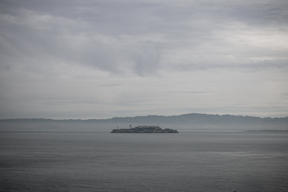 Alcatraz Island  ( /ˈælkəˌtræz/ ) is located in  San Francisco Bay , 1.25 miles (2.01 km) offshore from  San Francisco ,  California ,  United States . [2]  The small island was developed with facilities for a  lighthouse , a military fortification, a military prison (1868), and a  federal prison  from 1934 until 1963. [5]  Beginning in November 1969, the island was occupied for more than 19 months by a group of  Native Americans  from San Francisco, who were part of a wave of Native  activism  across the nation, with public protests through the 1970s. In 1972, Alcatraz became part of a national recreation area and received designation as a  National Historic Landmark  in 1986.  Today, the island's facilities are managed by the  National Park Service  as part of the  Golden Gate National Recreation Area ; it is open to tours. Visitors can reach the island in a little under 15 minutes by  ferry  ride from Pier 33, located between the  San Francisco Ferry Building  and  Fisherman's Wharf, San Francisco .  Hornblower Cruises and Events, operating under the name Alcatraz Cruises, is the official ferry provider to and from the island.  Alcatraz Island is home to the abandoned prison, the site of the oldest operating  lighthouse  on the  West Coast of the United States , early military  fortifications , and natural features such as  rock pools  and a  seabird  colony (mostly  western gulls ,  cormorants , and  egrets ). According to a 1971 documentary on the history of Alcatraz, the island measures 1,675 feet (511 m) by 590 feet (180 m) and is 135 feet (41 m) at highest point during mean tide. [6] However, the total area of the island is reported to be 22 acres (8.9 ha). [2]