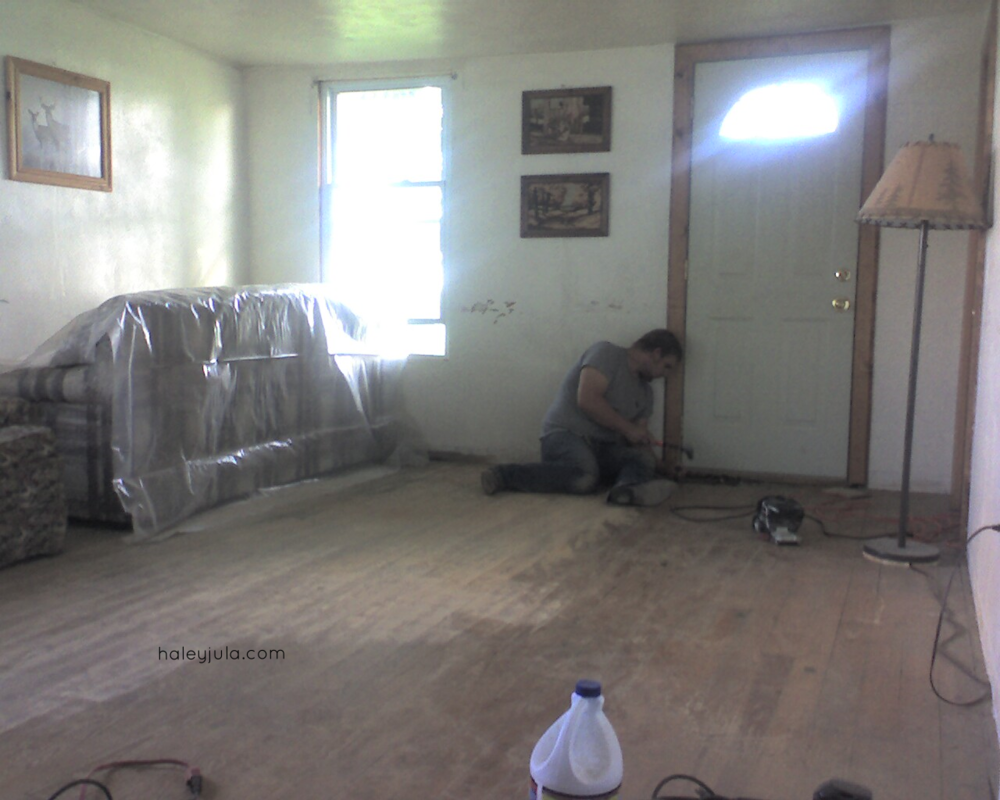 South Wall 'Before'. We hung a picture over the chimney opening. Todd is working on the floor.
