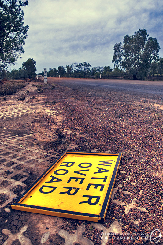 Downed sign: Water Over Road. Castlereagh Highway, northern New South Wales. The egg-crate stuff on the sides of the road is textured concrete, designed to prevent it from being washed away in flood water. (It doesn't work.)