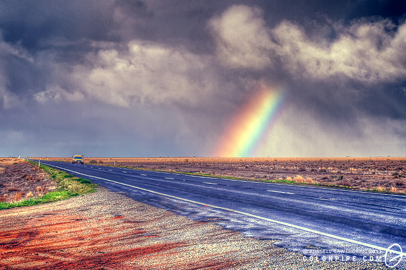 A yellow Holden Premier panel van travels beneath a rainbow on the Sturt Highway near Hay, New South Wales, Australia.