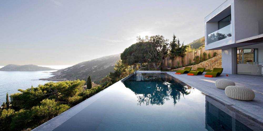 wonderful-infinity-swimming-pool-design-ideas-with-beautiful-sea-panorama-also-glass-balustrade-plus-green-lounge-patio-and-modern-shape-villa-architecture-as-well-as-wooden-fence-best-garden.jpg