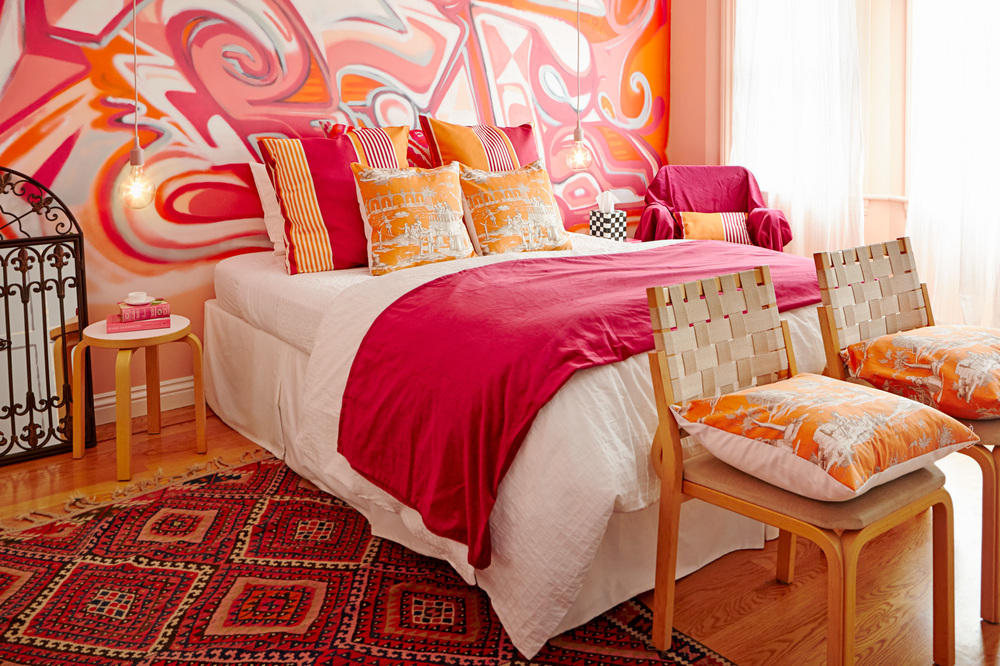 This colorful bedroom owes its color scheme to a Ken Done print. The room combines a graffiti mural by local artist Nicolas Held; toile, ikat, and striped fabric, and antique rug for an eclectic playful vibe.