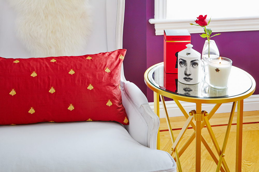A custom made silk pillow with Napoleonic bee motif is paired with a Fornasetti candle with its own bee, the Gueridon table by Ballard designs is custom painted.