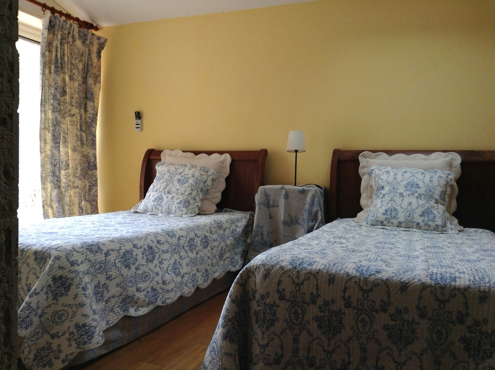 View of two beds and toile curtains.