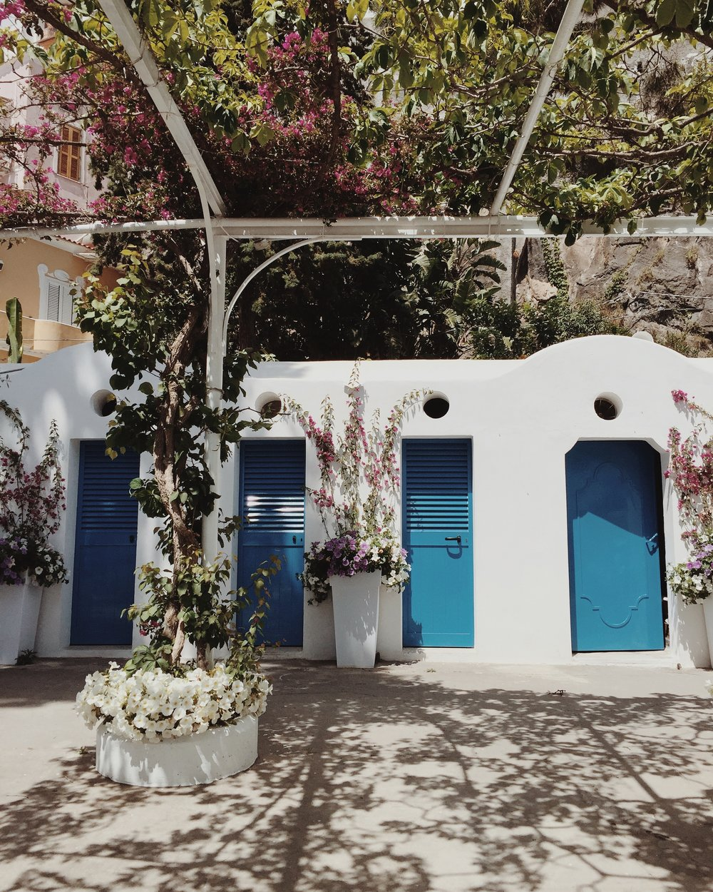 Blue doors against white stone EAT.PRAY.MOVE Yoga Retreats | Amalfi Coast, Italy