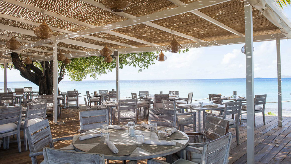 // Mustique →<p>After a day in its crystal clear waters, you'll suddenly feel transported to southern France with Mustique's ample seaside cafes.</p>