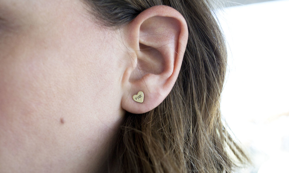 Tiny heart shaped earring stamped with FUCK on a model's ear