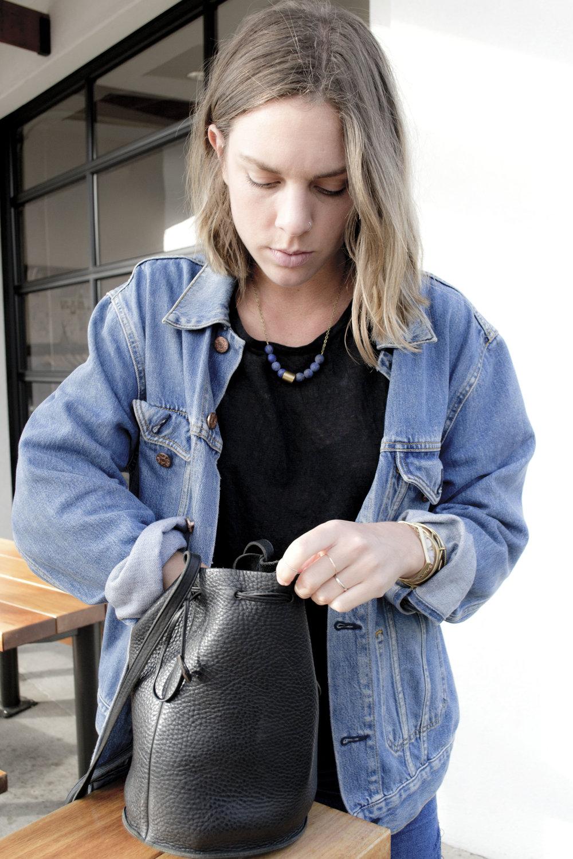 model reaching into purse.