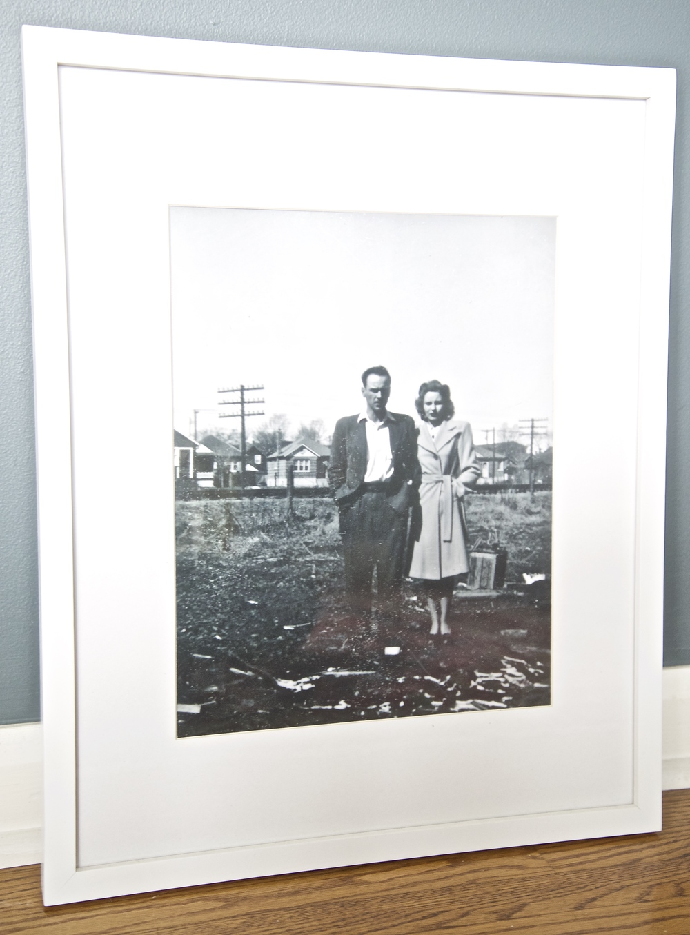 This black & white photograph is a portrait of my grandparents. My husband surprised me & had it blown up from the original copy. To say I love it would be an understatement! The placement of the poles in the background adds to the street scene behind them.