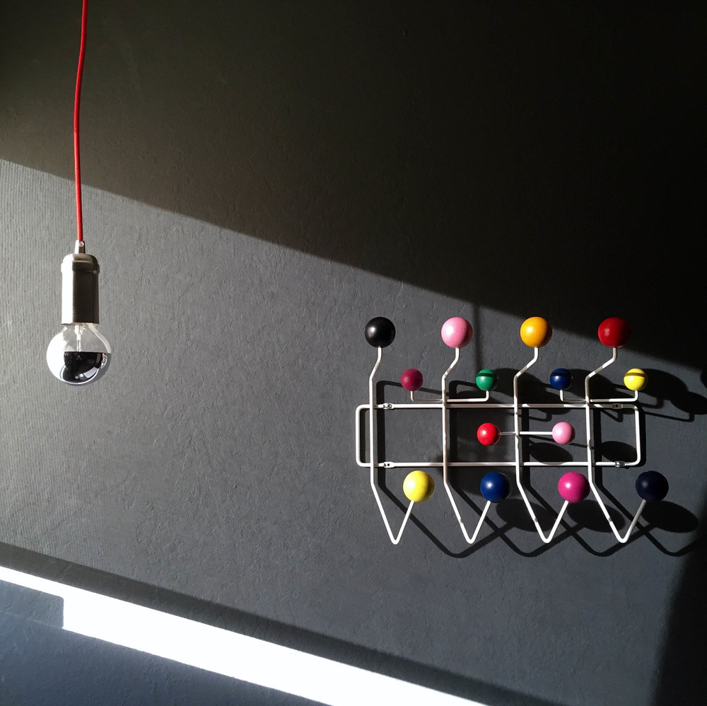 Is it crazy that I'm jealous of a toddler's bedroom. The Eames Hang-It-All hooks are the perfect pop of color on this dark grey wall.