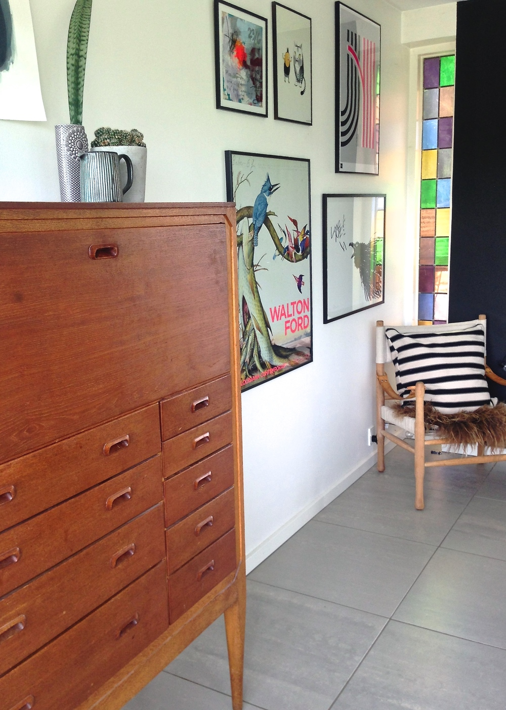 """The first furniture my grandmother bought (before she met my granddad) were designs from some of the greatest designers/architects in Denmark from the 1950´s. I have inherited some chairs and a cabinet from her. I love furniture (especially teak) from the 1950´s but also German Bauhaus interior."" The eclectic collection of artwork throughout the home is amazing. I will never tire of a good gallery wall, we have several in our own house. The original stained glass is the perfect addition to this corner. Those colours make me smile."