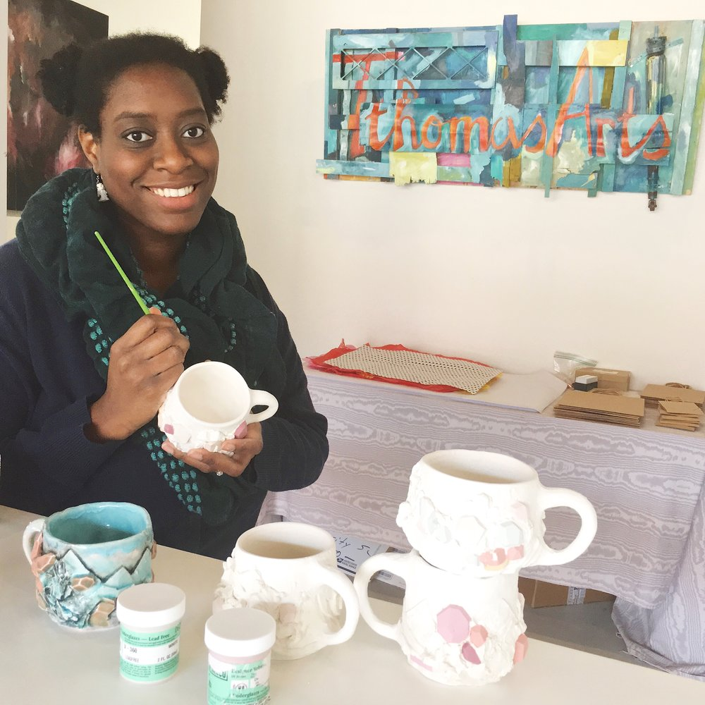 Tiffany in her studio hand painting porcelain mugs that are very popular in her online shop.