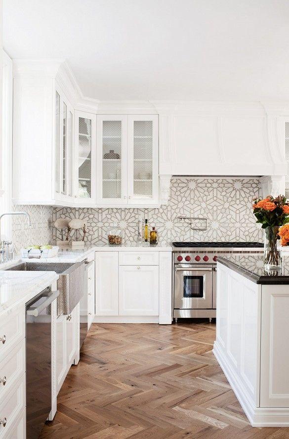 white kitchen with goemetric backsplash and wood floors