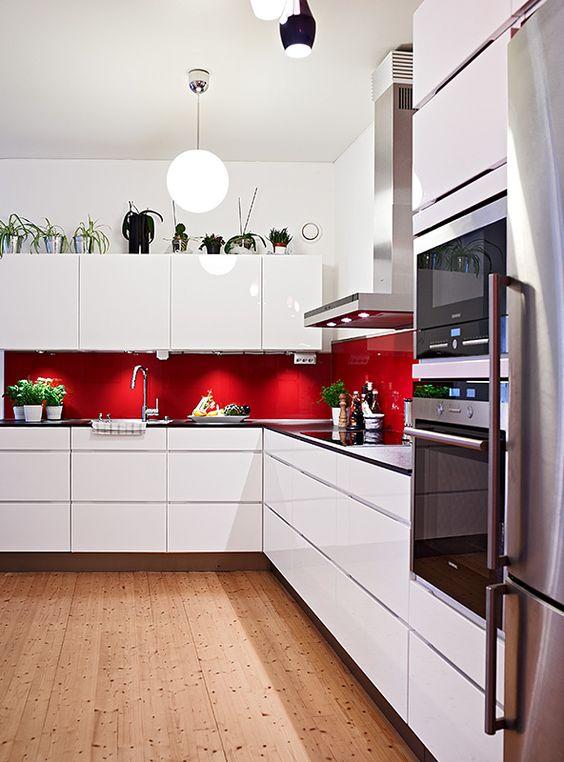 minimalist white kitchen with red backsplash