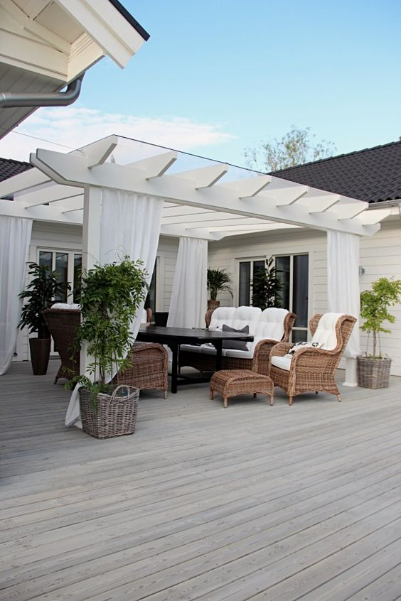 charming white deck pergola with wicker furniture