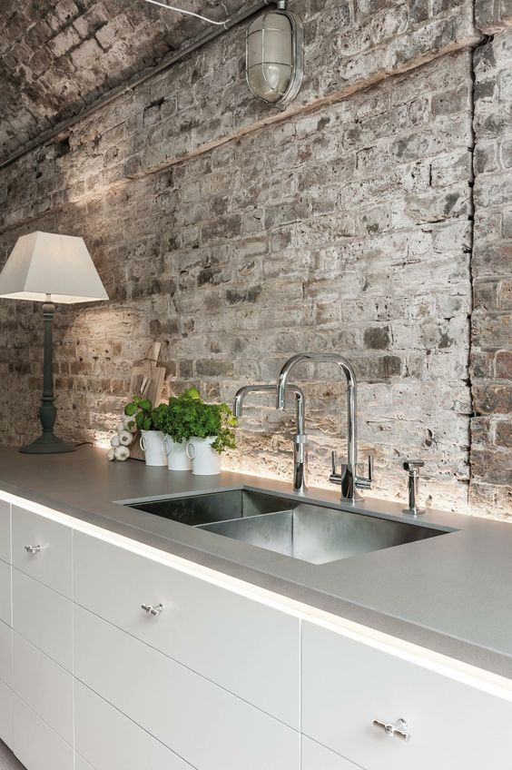 white modern kitchen with rough brick wall