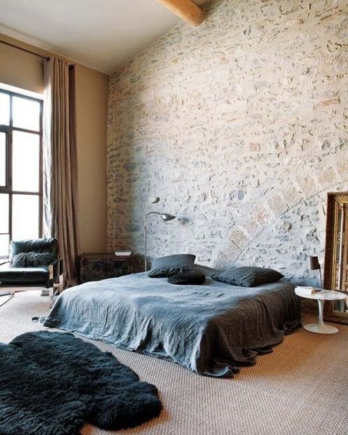 spacious bedroom with rough brick wall