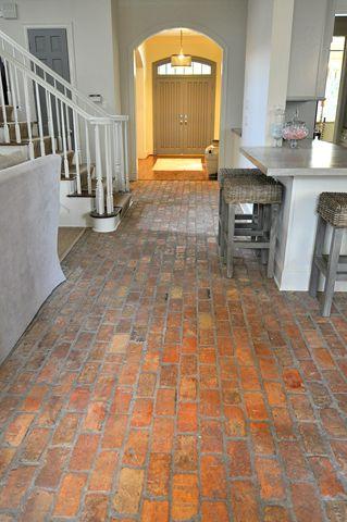 hallway with warm red brick floor