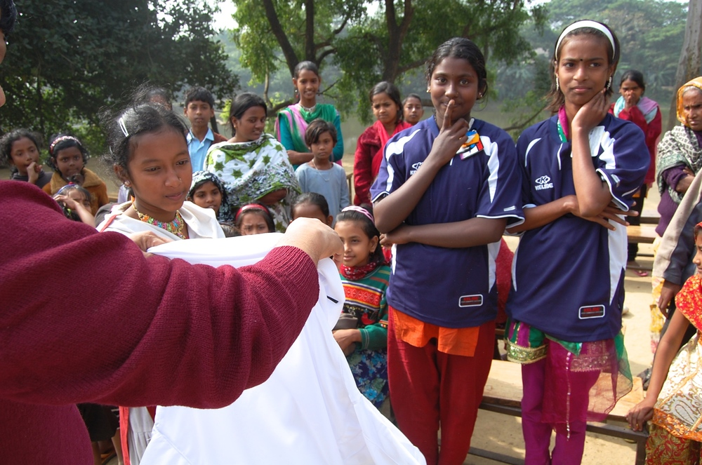 Distributing soccer gear to girls
