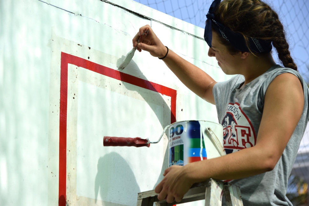 Hannah painting the basketball backboard