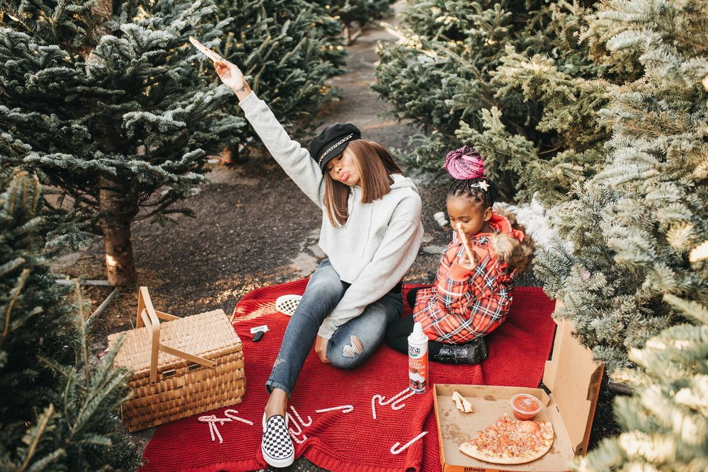 10 Things to Add to your Holiday Bucket List: image of a mom and daughter eating pizza at a Christmas tree farm