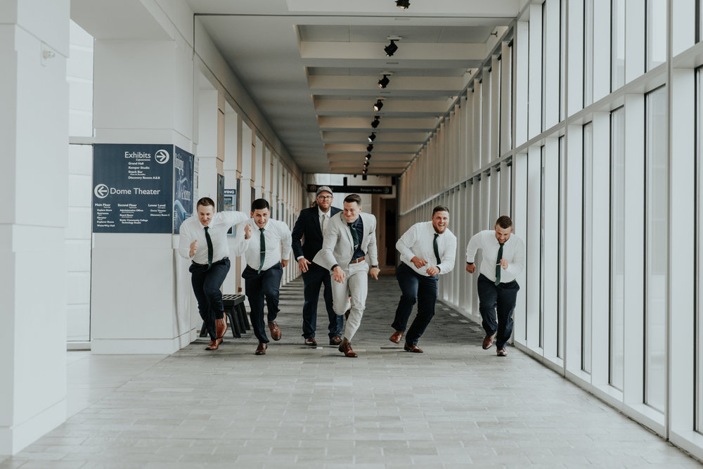 Groomsmen playing around at wedding | Be Images