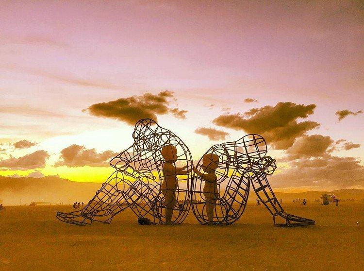 Burning Man holding hands