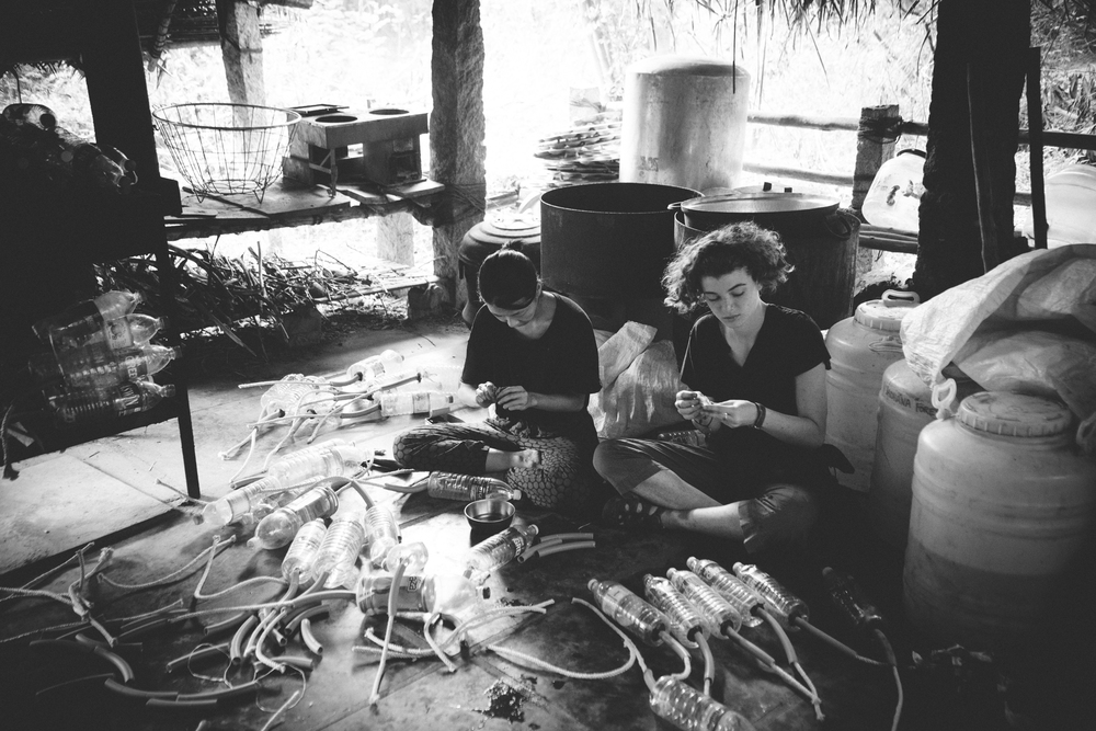 Peggy and Emmy making wicks out of plastic bottles meant to be used in the irrigation process.