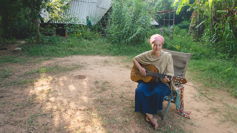 Strumming a few beautiful melodies to 'gather all the children of the earth and sun' once she is done waking up the sleeping.
