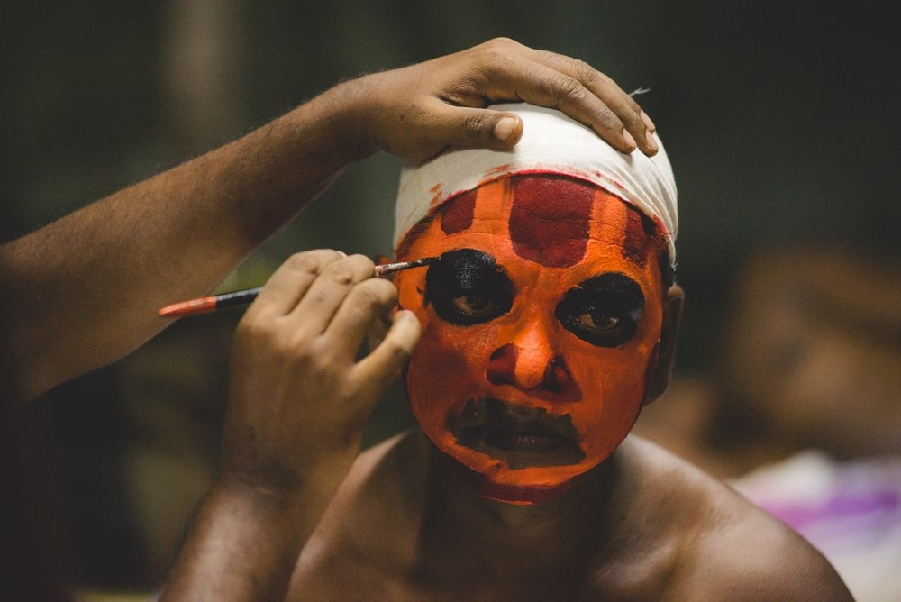 Some backstage footage of one of the dancers being readied by the makeup artist. The troupe comprises of backward or lower class of people who used to be (and in many places, are still) not treated as equals by the upper caste. But during the time of Theyyam, they dawn their makeup and are treated as Gods even by the upper caste.
