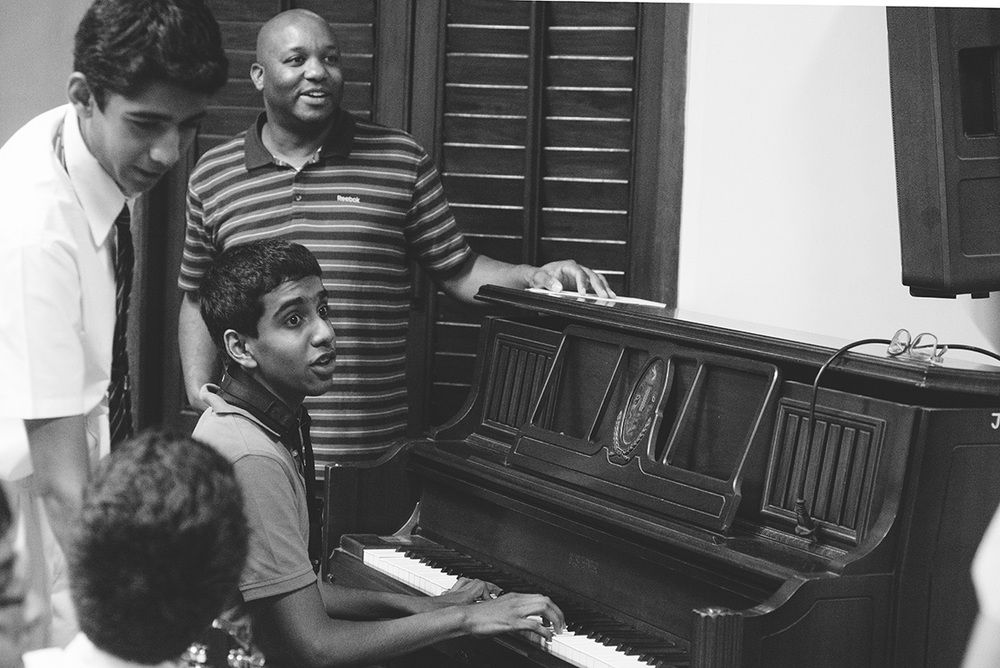 Mark Copeland interacting with a few students from the school, helping them with some piano lessons.