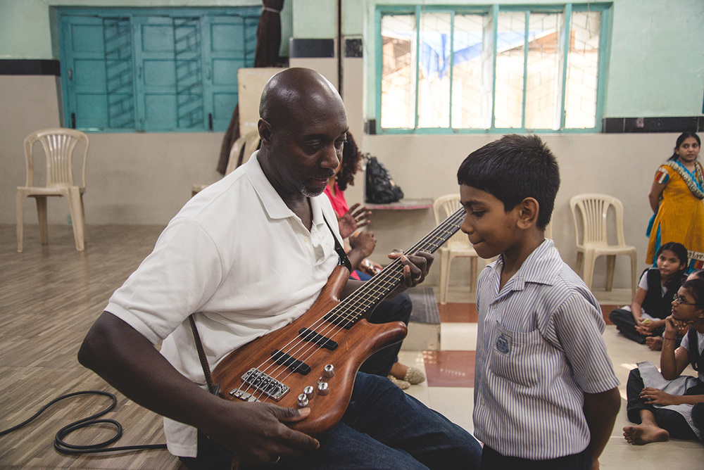 A curious kid approaches Winston and asks him how his bass produces those sounds. Winston patiently explains.
