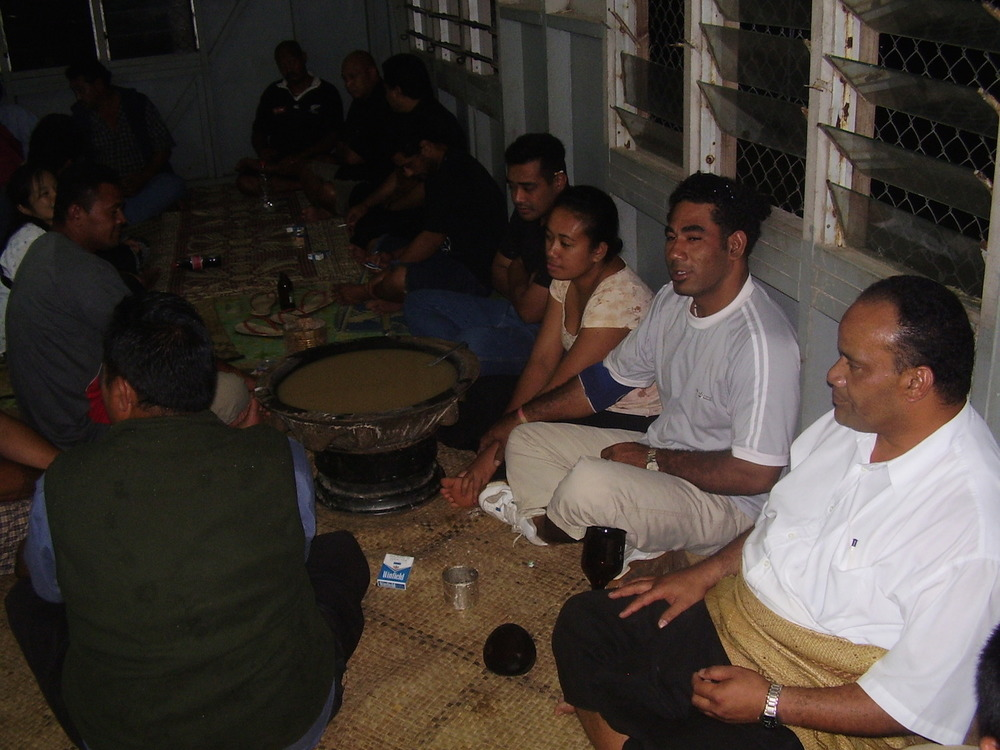Pic: The female custodian of the Kava pot, surrounded by the male drinkers