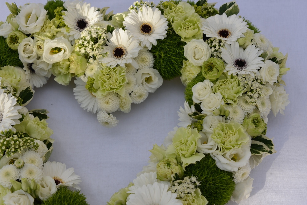 Our designs are full of flowers from edge to edge. This popular heart wreath is ideal for family or friends to send and this late summer one featured green centred garden roses,lovely double crisp white lisianthus, bold black centred gerberas, dainty white eupatorium, unusual green fluffy dianthus and tiny pom pom chrysanthemums.