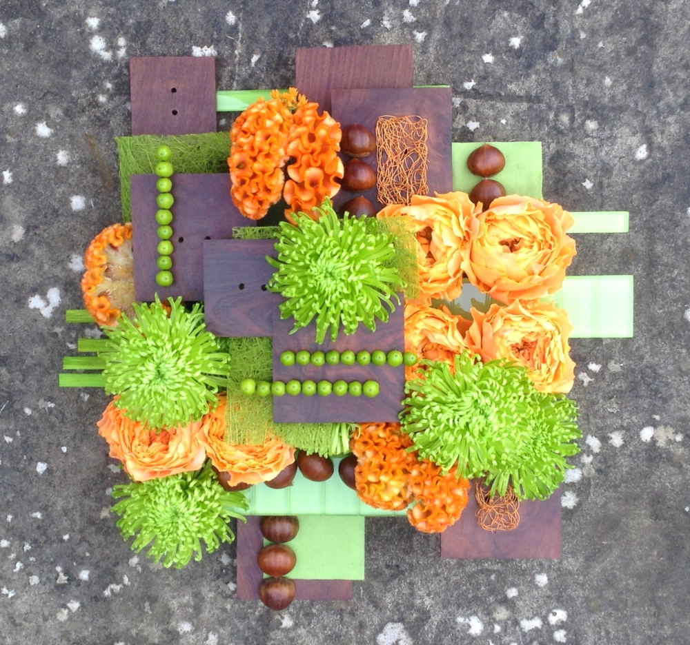 A layered, textured design for advanced arrangers using vibrant green chrysanthemums, velvety orange celosia and gorgeous orange garden roses.