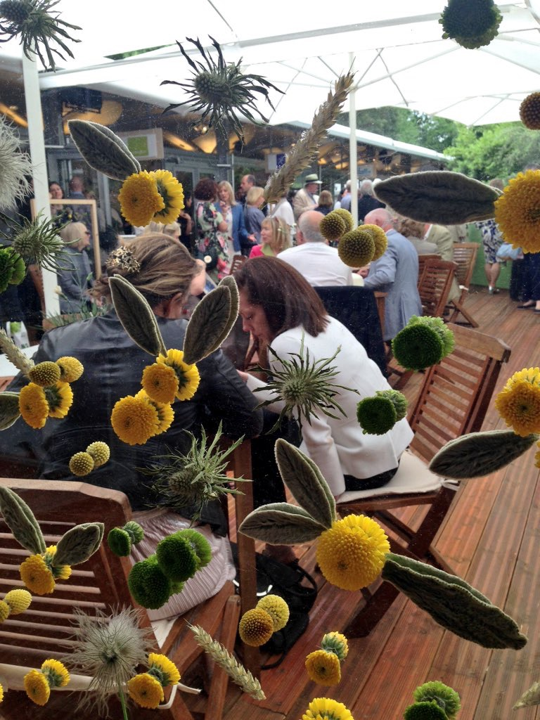Transparent screens decorated with glued flowers in bright sunny shades of yellow sheltered visitors in the garden bar.